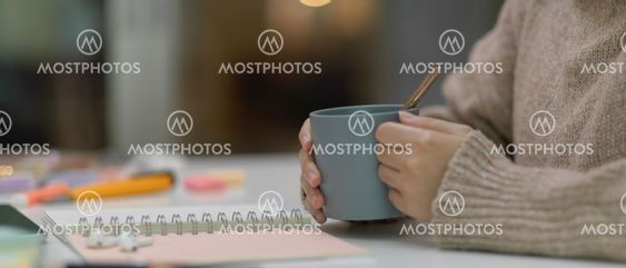 Female student holding cup while sitting at study table