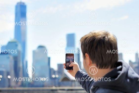 Tourist taking mobile photo of skyscrapers