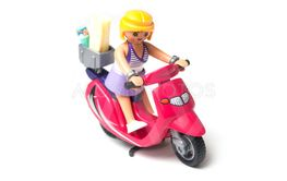 Playmobil figurine on red scooter on white background
