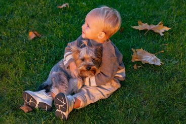Happy baby playing with little dog at autumnal nature....