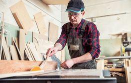 Carpenter worker cutting wooden board