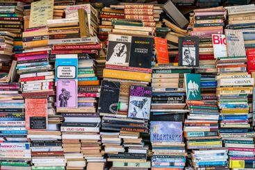 Många böcker i höga travar utomhus till försäljning.
