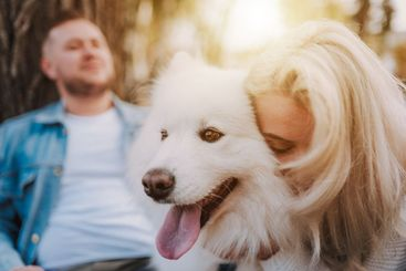 Happy couple spending time outdoors with their pet dog