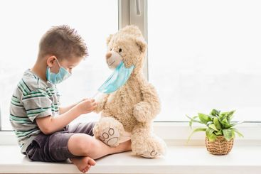 A small child helps a teddy bear put on a medical mask...
