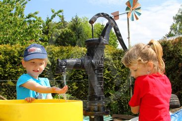The girl and the boy at the water pump
