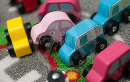 miniature wooden cars on road carpet on the floor