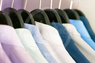 Several men's shirts of different colors on the hangers....