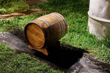Oak barrel for storage wine lies on special support in yard