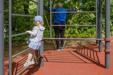 Little girl climbing a ladder on a sports field. Healthy...