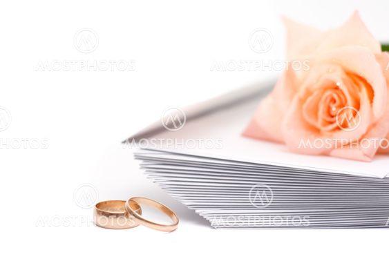 Rose, kuvert och Vigselringar på vit bakgrund