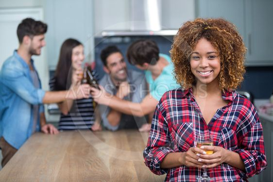 Smiling woman holding wine while friends in background