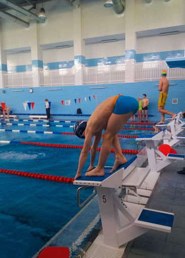 Training swimmers. A teenage boy is preparing to jump...
