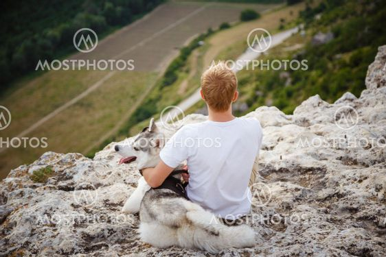 hiker with siberian husky dog looking at beautiful view...