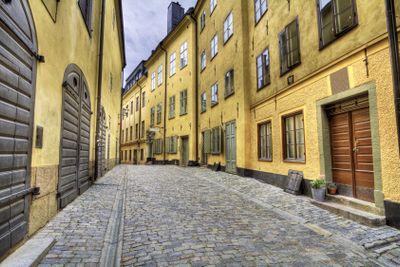 Cobblestone street with yellow houses.