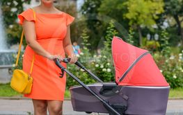 Mother attending to her infant baby in a pram