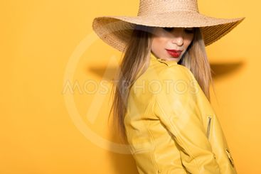 attractive asian female model in straw hat posing on...