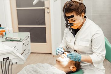 Dentist young woman treats a patient a man. The doctor...