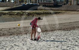 Portrait of girl cleaning beach with plastic bag