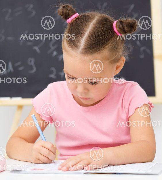Liten flicka skriver med pennan