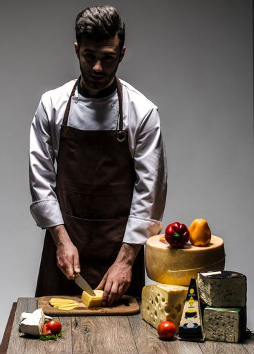 young chef with cheeses