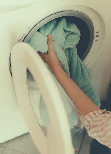 House cleaning. Woman putting towel in washing machine.