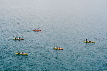 A group of tourists travel in pairs kayaks by sea, near...