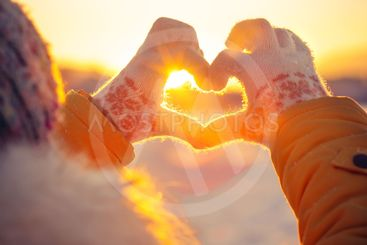 Woman hands in winter gloves Heart symbol shaped...