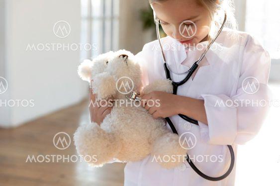 Little girl in white uniform examine plush toy
