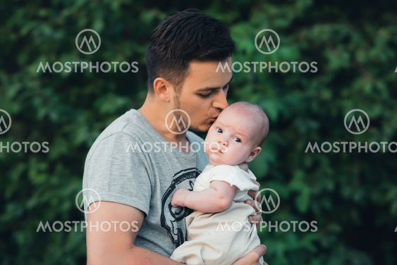 young Caucasian dad with beard hugs newborn baby boy son