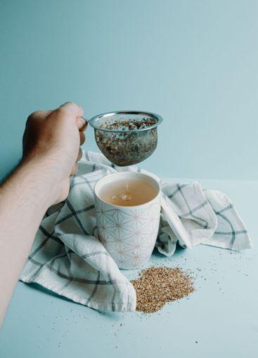 A hand grabbing a tea distiller over a cup of tea over a...
