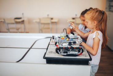 Two schoolgirls study in a robotics class, assemble a...