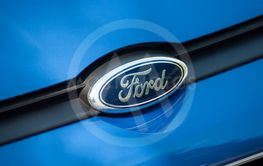 Ford logo on blue car front parked in the street