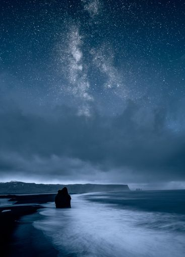 Ocean and coastline at night against starry sky