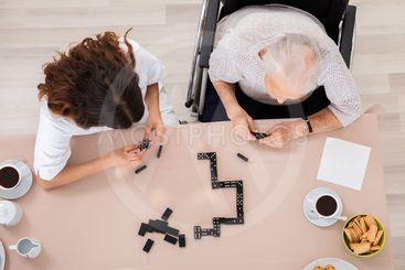 Elder Woman Playing Domino Game With Her Nurse