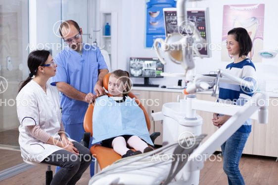 Dentist assistant preparing kid patient for tooth...
