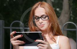 Beautiful young redhead woman with a tablet-pc in the...