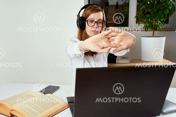 Woman in the headphones streching arms after long...