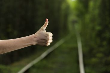 Like it. Thumb up with natural bokeh background of leafy...