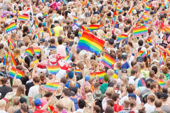 Pride parade in Stockholm with happy people and waving...