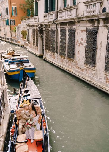 Italy wedding in Venice. A gondolier rolls a bride and...