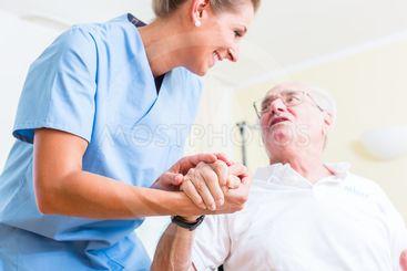 Nurse holding hand of senior man in rest home