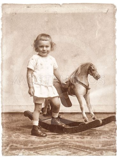 old photo of little girl with rocking horse toy.nostalgic...