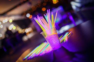 Multicolored UV fluorescent sticks in a glass at a...