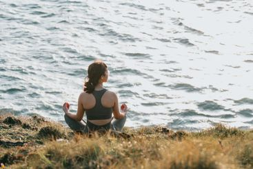Young fit woman doing yoga in the rocks of a wild coast...