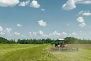 Agricultural machinery, a tractor collecting grass in a...