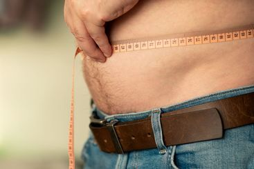 Closeup of measuring a male belly with a tailor's meter