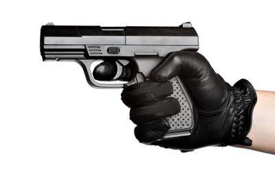 Hand Pointing a Black Handgun