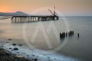 Seascape with deserted jetty during sunset