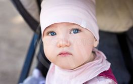 close up portrait of cute little girl in baby carriage