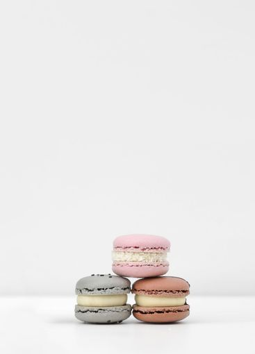 three colored, pink, brown and gray french macarons or...